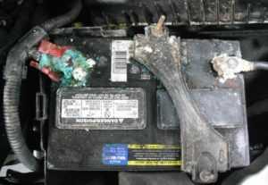 Грязный автомобильный аккумулятор с окисленными клеммами